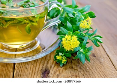 Flowers Rhodiola rosea, an herbal tea in a glass cup on a wooden boards background