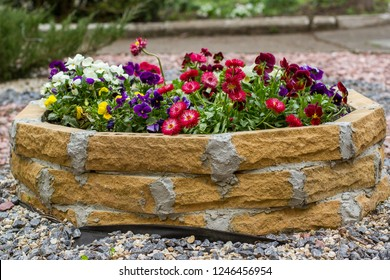flowers in a round flowerbed in the garden. Round stone flower bed with flowers on the street. Raised Circular Red Brick Flowerbed