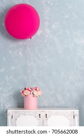 Flowers in round luxury present box and big pink balloon on chest of drawers. Bouquet of pink and white peonies in paper box. Interior decoration in in pastel colors. Free copyspace for text.