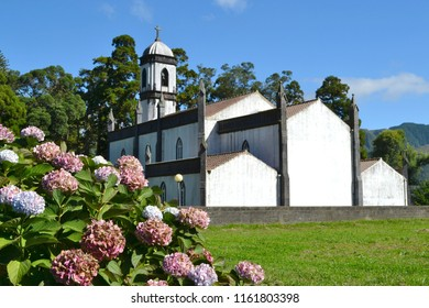 Flowers and Saint Nicolas Church (built in 1857) in Sete Cidades on Sao Miguel Island, Azores, Portugal. As seen from the road leading to the village.