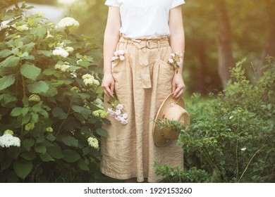 flowers and shrubs in summer Ornamental garden. girl woman in linen skirt and hat on path of Park. Gardening and Landscaped