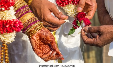 Flowers and silk is split between the groom and priests hands next to the henna covered hand of the bride during the vowels part of a South Indian wedding ritual