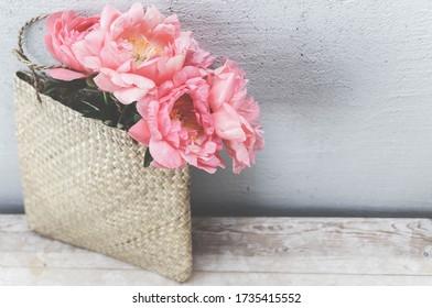 Peonies flowers in straw bag. Retro vintage background. Romantic greeting card.