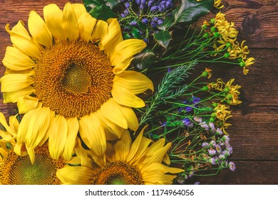 flowers of a sunflower and field grass on a wooden background.
