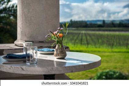 Flowers and Vase with Brunch Settings rest on Marble Round Table in front of Pillar and Vineyard in Sonoma, CA