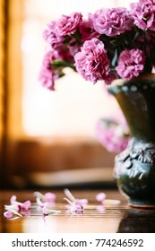 flowers in a vase, flowers on the table, fallen petals, carnation