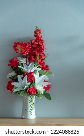 Flowers in vase on the table with light blue background wall.