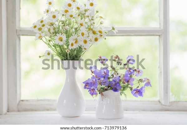 flowers in vases on windowsill