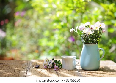 Flowers with vintage pot and heart shaped cup on wooden table