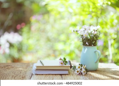 Flowers with vintage pot and notbooks on wooden table