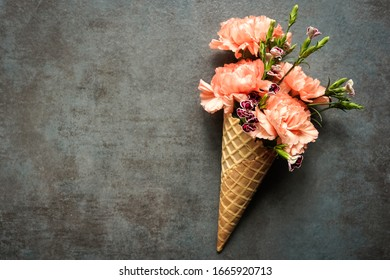 Flowers in a waffle ice cream cone. Fun, background image. Orange, peach carnations and small purple flowers. Flat lay image.