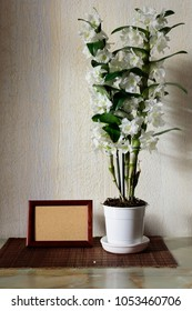 Flowers of White Nobile Dendrobium and frame on the table in the room