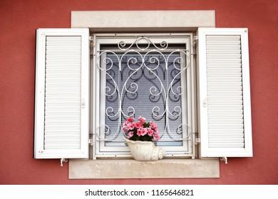 Flowers in a white old window. Piran, Slovenia