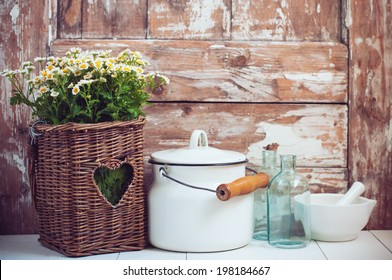 Flowers in a wicker basket, glass bottles and vintage milk can on wooden background, cozy home rustic decor, cottage living