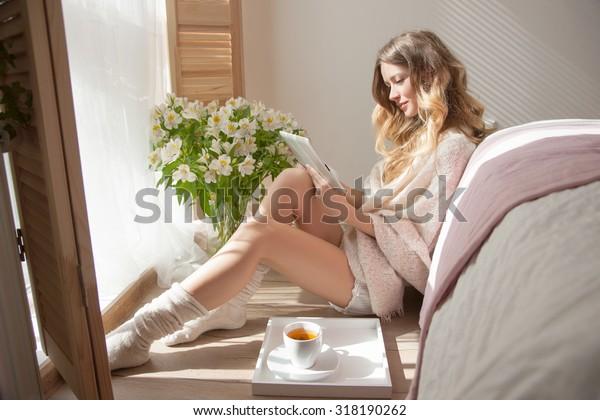 女性の寝室にある花は、香りが女性を連想させる。寝室に日が差し込み、女の子は花の背景に読書をしている。心地よいイメージ、朝の魅力的なモデル、リラックスできる日
