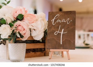 Flowers in a wooden box and number of a table on the wooden plate