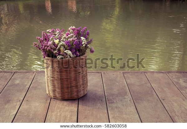 Flowers in wooden vase beside the river.
