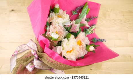 Flowers wrapped in pink tissue and hessian modern trend wrapping flat lay for Mother's Day, birthday or Valentine's Day celebrations.