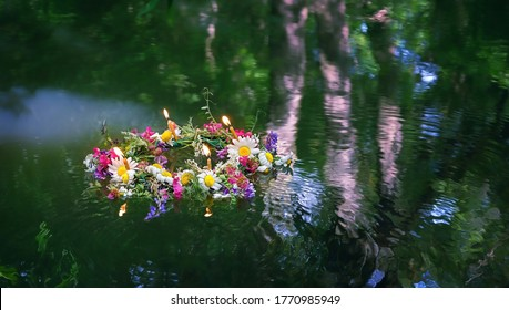 flowers wreath with burning candles in water. old national tradition, fortune telling for pagan holiday Ivan Kupala. Summer Solstice Day, Midsummer. wiccan symbol and rituals
