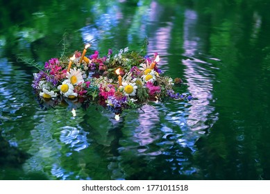 flowers wreath with burning candles in water. old national tradition, fortune telling for pagan holiday Ivan Kupala. Summer Solstice Day, Midsummer, wiccan Litha sabbat rituals