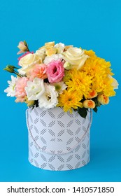 flowers: yellow single-headed and shrub roses, yellow chrysanthemum, pink eustoma, white eustoma in a hat box on a blue table close-up with a blurred background