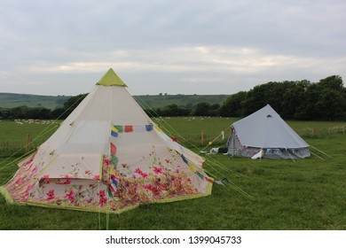flowery tipi and bell tent in field