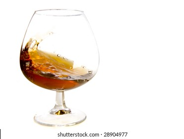 flowing cognac in glass on white ground