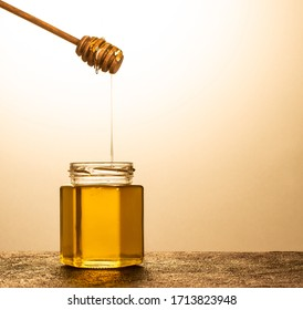 Flowing honey from dipper  in a glass jar on yellow background.