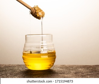 Flowing honey from wooden dipper in a glass jar on golden background.