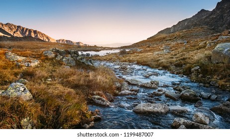 Flowing mountain river in High Tatras landscape near Rysy peaks at sunset, Slovakia.