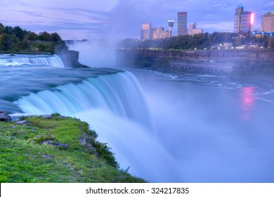 Flowing Niagara Falls from the American side with the skyline of the city of Niagara Falls in the background at dawn. The Niagara Falls is one of the largest and most famous waterfall in the world.
