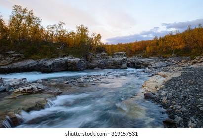 Flowing river in Abisko national park in Sweden at sunset