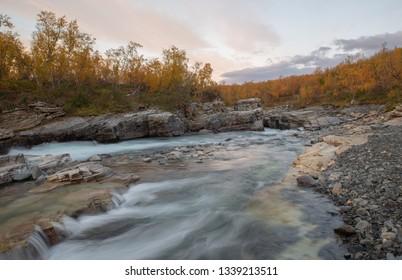 Flowing river in autumn. Abisko national park in Sweden