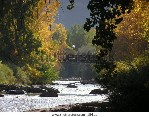 Flowing river with foot bridge in the distance.