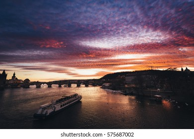 Flowing river to historic bridge (Charles Bridge) at sunset that colors the clouds of reddish purple color. On river cruise ship sailing downstream. Entire picture is very dark in warm sunset colors.
