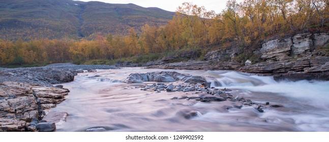 Flowing river landscape in sunset. Abisko national park in sweden
