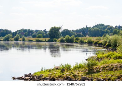 Flowing river and lots of vegetation on the shore. A beautiful summer view.