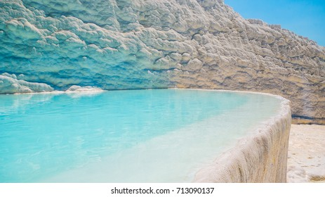 Flowing slowly down the huge mountainside, mineral water collect in terraces, dripping over balconies of stalactites into milky pools.  Pamukkale, Turkey.