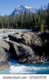Flowing water of Natural Bridge in Yoho National Park with mountains and trees in background