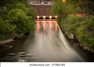 Flowing Water from the Out Flow of a Hydro Electric Power Plant with Green Trees Blowing in the Wind - Minneapolis, Minnesota.