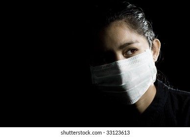 flu alarm: protective face mask on beautiful asian woman. low-key picture.