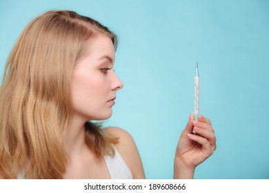 Flu cold grippe. Woman having high temperature. Sick girl with fever checking mercury thermometer on blue.