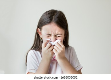 Flu concept - Upset and sick child blowing his nose with flu symptoms coughing at home, Allergic girl, flu season. Girl with cold rhinitis, cold