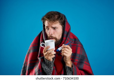 flu, immunity, health, a man in a warm plaid drinks hot tea keeps a thermometer on a blue background