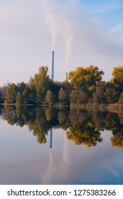 Flue chimney of a cogeneration plant, autumn landscape, lake and trees. Ecology and environmental pollution