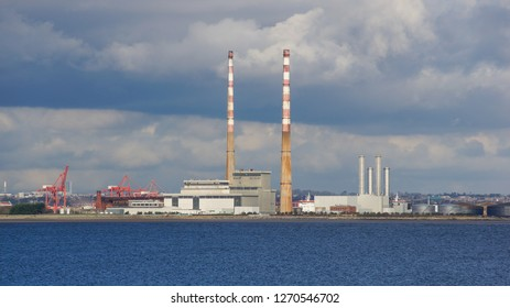 Flue-gas stacks/chimneys of a decommissioned waste incinerator  next to the buildings of a new Waste to Energy Facility. Industrial landscape on the Poolbeg peninsula in Dublin, Ireland.