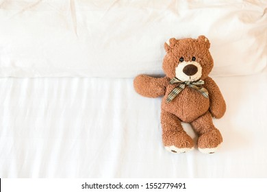 Fluffy brown teddy bear lying down on the bed alone with space on white bed sheet