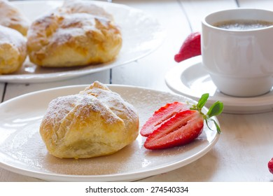 Fluffy bun of puff pastry with strawberry filling and coffee