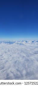 Fluffy clouds, blue sikies and snow covered alps peaks