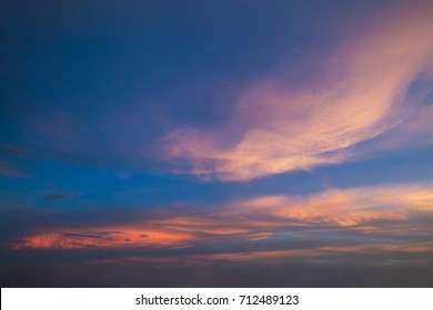 fluffy clouds in sunset sky.